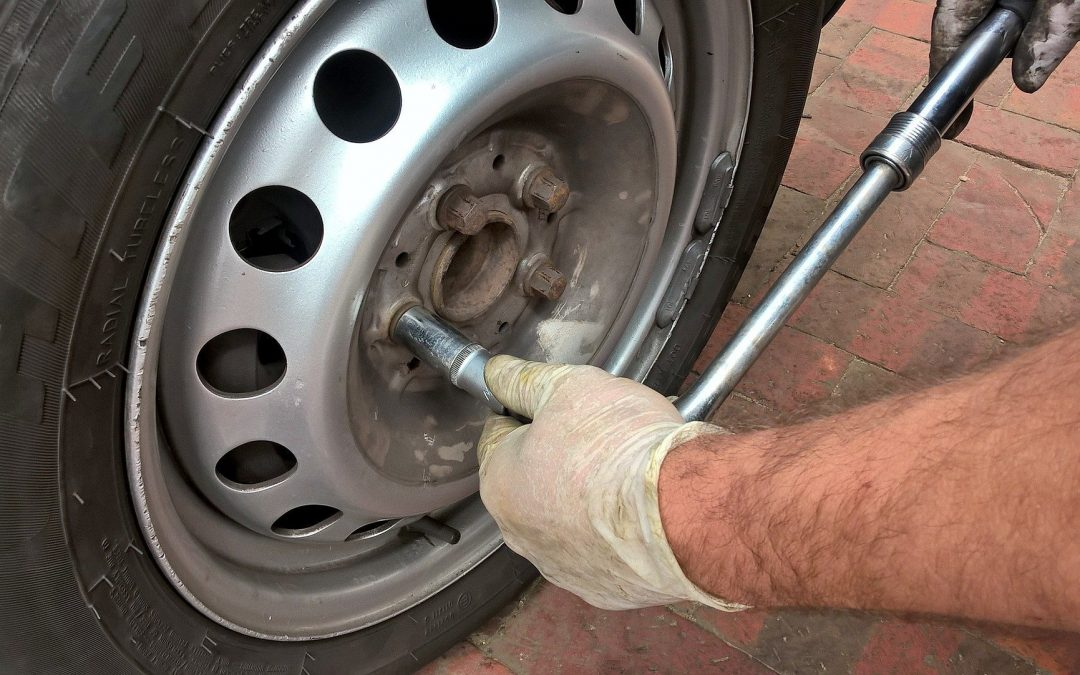 Mechanic wearing gloves and tightening a bolt on a tyre on a pavement