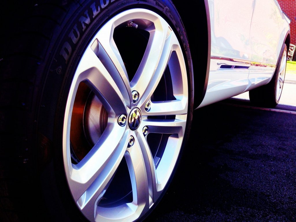 A white car sporting a Dunlop tyre with shiny rims on a parking lot