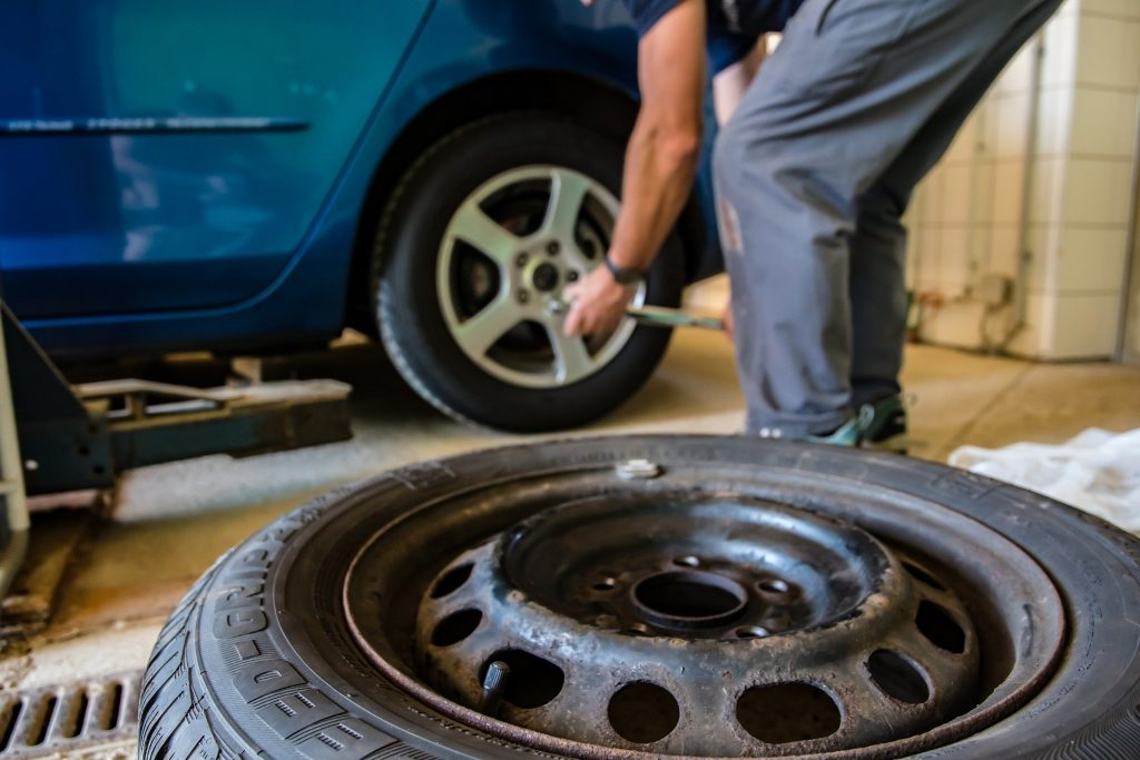 A close up of a spare tyre and a mechanic replacing tyres of a blue car in the background