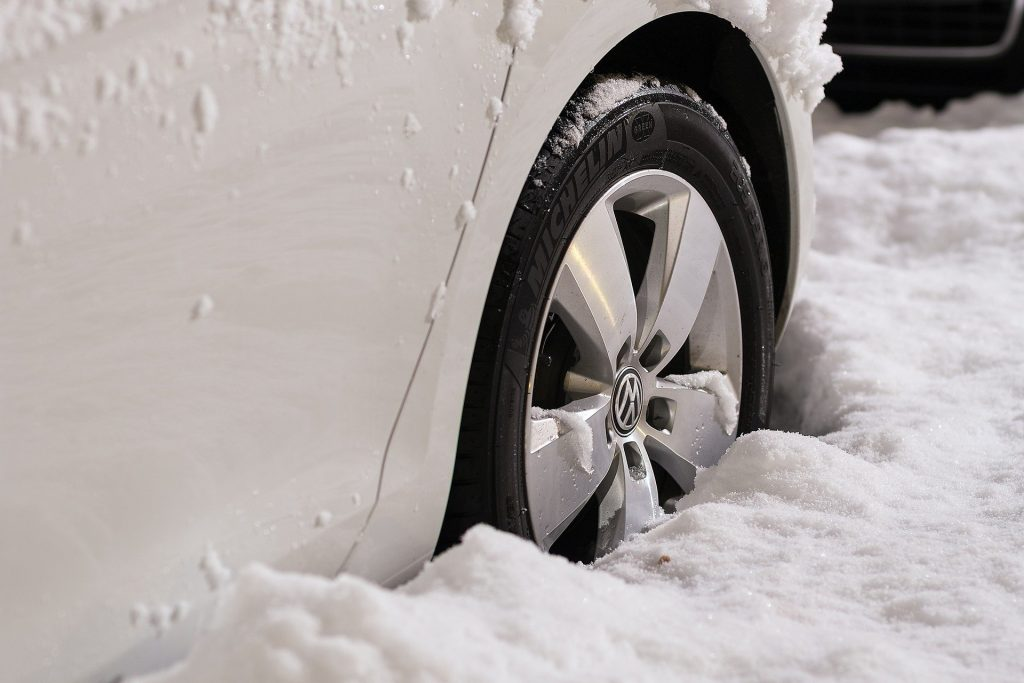 Right front tyre of a white car party buried in snow.